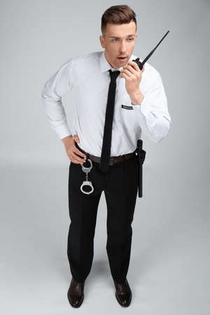 Male security guard using portable radio transmitter on color background