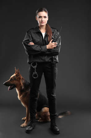 Female security guard with dog on dark background