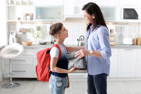 Jeune femme aidant son petit enfant à se préparer pour l'école à la maison Banque d'images