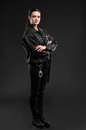 Female security guard in uniform on dark background