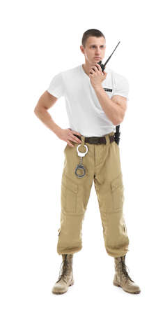 Agent de sécurité masculin à l'aide d'un émetteur radio portable sur fond blanc