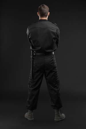 Male security guard in uniform on dark background Banque d'images