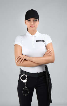 Female security guard in uniform on color background