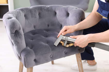 Male worker removing dirt from armchair with professional vacuum cleaner indoors, closeup