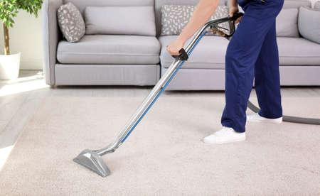 Pracownik płci męskiej usuwający brud z dywanu za pomocą profesjonalnego odkurzacza w pomieszczeniach