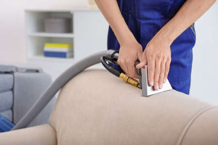Dry cleaning worker removing dirt from sofa indoors Stock Photo