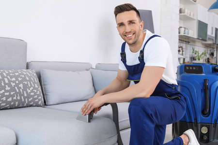 Male worker removing dirt from sofa with professional vacuum cleaner indoors