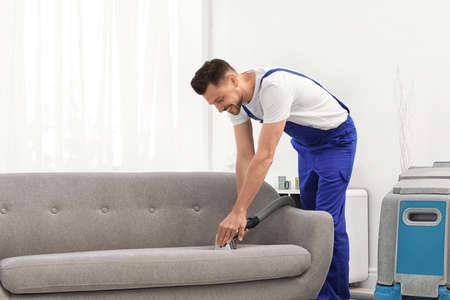 Dry cleaning worker removing dirt from sofa indoors Stockfoto