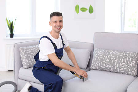 Dry cleaning worker removing dirt from sofa indoors Foto de archivo