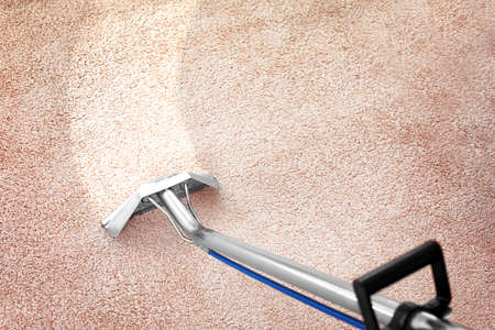 Removing dirt from carpet with professional vacuum cleaner indoors Archivio Fotografico