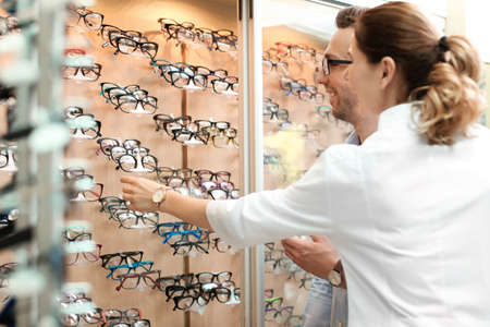 Female ophthalmologist helping man to choose glasses in optical store