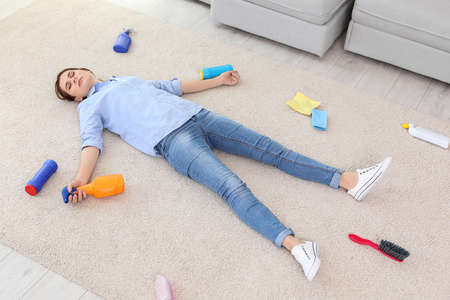 Tired woman lying on carpet surrounded by cleaning supplies