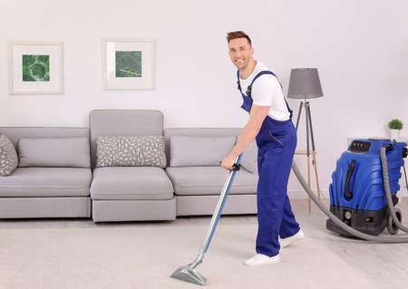 Trabajador masculino quitar la suciedad de la alfombra con aspiradora profesional en interiores