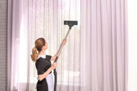 Female worker removing dust from curtains with professional vacuum cleaner indoors