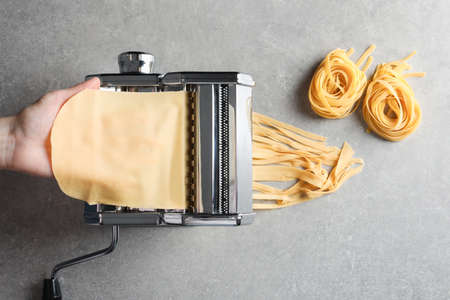 Young man preparing noodles on pasta maker at table, top view Stock Photo