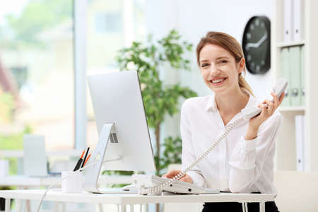 Female receptionist talking on phone at desk in office