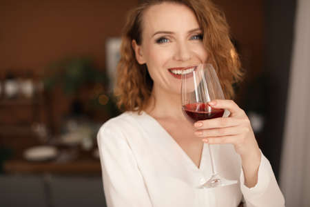 Woman with glass of delicious wine indoors