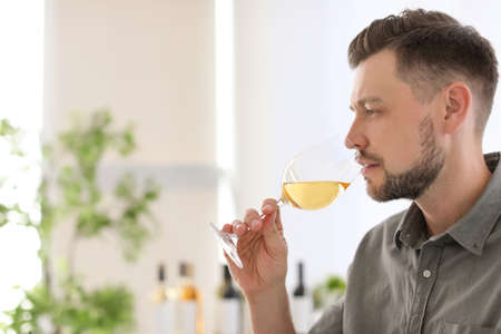 Young man with glass of wine indoors