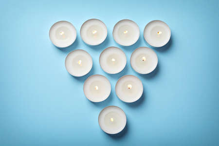 Burning wax candles on color background, top view Stock Photo