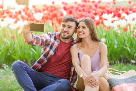 Happy young couple taking selfie in green park on sunny spring day