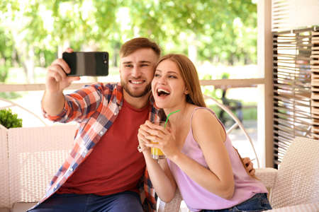 Happy young couple taking selfie in cafe on spring day