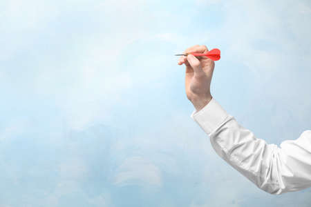 Man holding dart on color background. Business trainer concept
