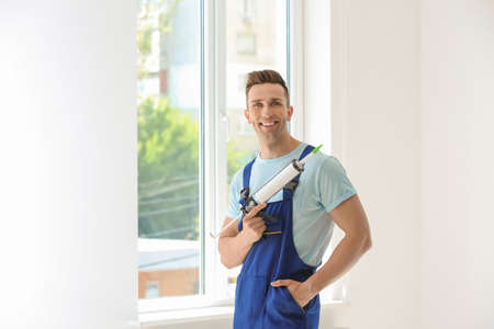 Construction worker in uniform with window sealant indoors