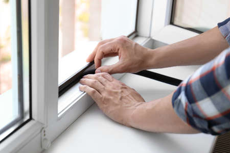 Young man putting sealing foam tape on window indoors Stock Photo
