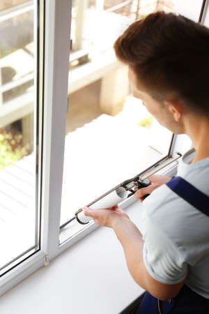 Construction worker sealing window with caulk indoors 스톡 콘텐츠