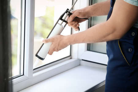 Construction worker sealing window with caulk indoors Stock Photo