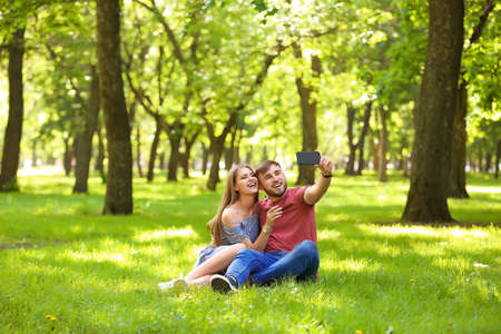 Happy young couple taking selfie on green grass in park