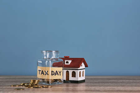 House model, glass jar with label TAX DAY and coins on table
