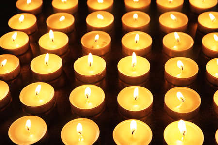 Wax candles burning on table in darkness, closeup
