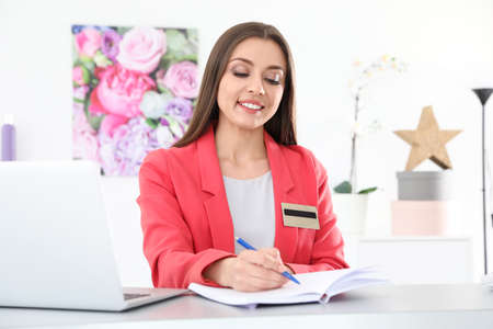 Beauty salon receptionist with notebook at desk