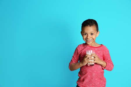 Entzückender afroamerikanischer Junge mit Glas Milch auf farbigem Hintergrund Standard-Bild