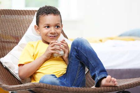 Entzückender afroamerikanischer Junge mit Glas Milch zu Hause