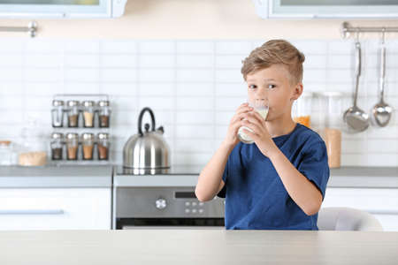 Adorable little boy with glass of milk in kitchen