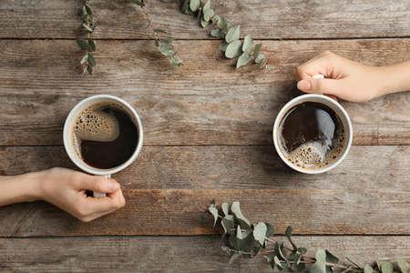 Junge Frauen mit Tassen des köstlichen heißen Kaffees auf hölzernem Hintergrund, Draufsicht
