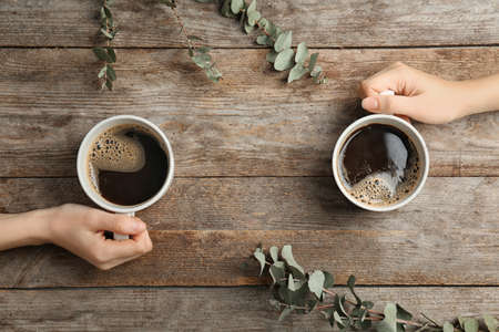 Young women with cups of delicious hot coffee on wooden background, top view Archivio Fotografico