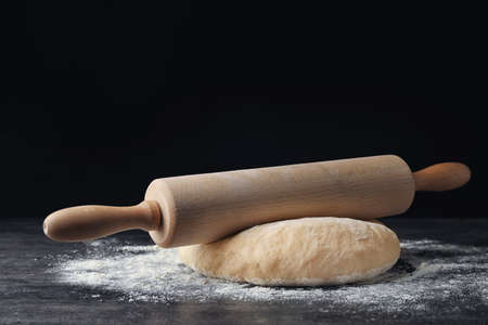 Raw wheat dough with flour and rolling pin on table