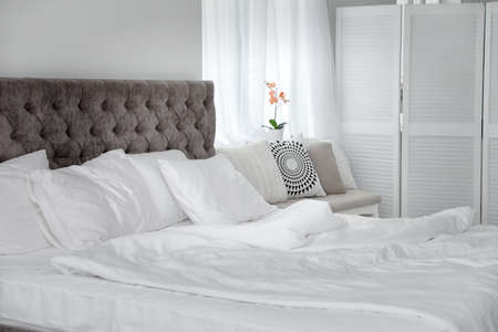 Bed with soft pillows in elegant room interior