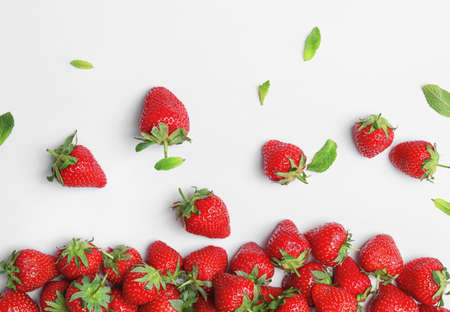 Composition with ripe red strawberries and mint on light background