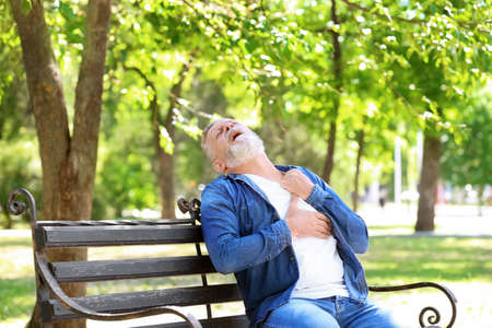 Mature man having heart attack on bench in park