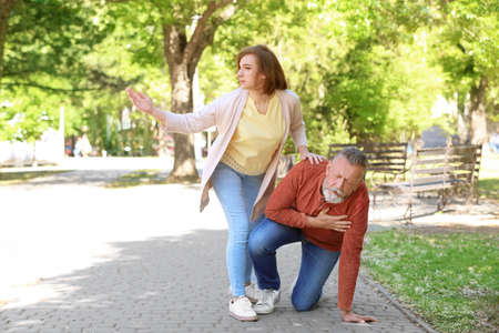 Woman helping mature man suffering from heart attack in park