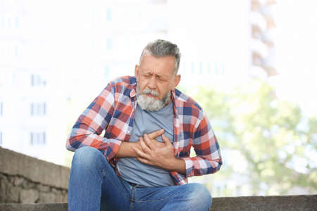 Mature man having heart attack, outdoors