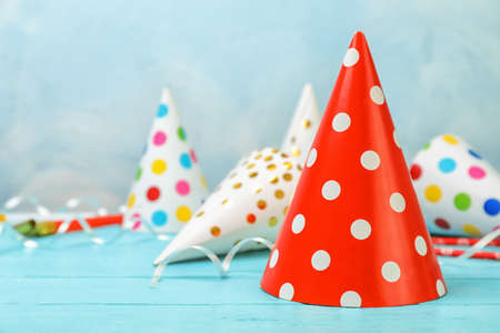 Birthday party caps on table against color background Stock Photo