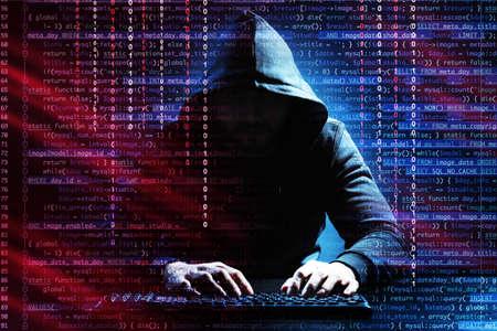 Hacker met toetsenbord aan tafel op donkere achtergrond. Concept van cyberveiligheid en aanval Stockfoto