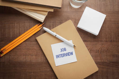 Note with text JOB INTERVIEW and stationery on table