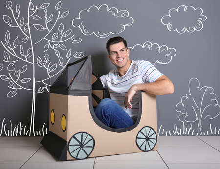 Young man in cardboard auto and drawn landscape on background. Dreaming of car