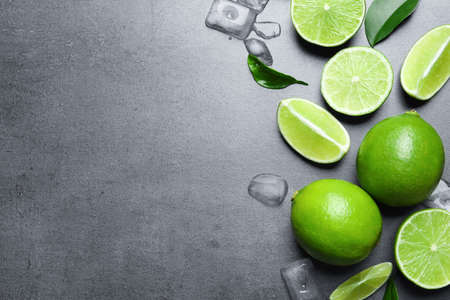 Fresh ripe limes and ice cubes on gray background, top view